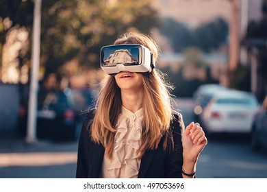 Surprised young beautiful girl gesture testing virtual reality 3D video glasses VR headset dressed in a office outfit gesture in the air with the hand touching augmented reality environment