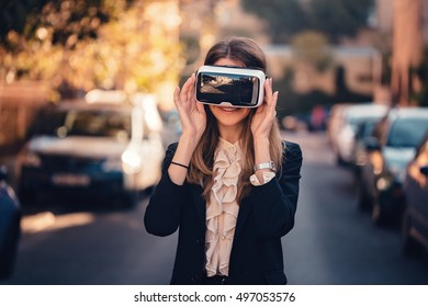 surprised young beautiful girl wearing virtual reality 3D video glasses VR headset dressed in a office outfit amazed by augmented reality on the street with beautiful autumn sun light colors