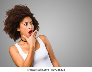 surprised young black woman covering her mouth