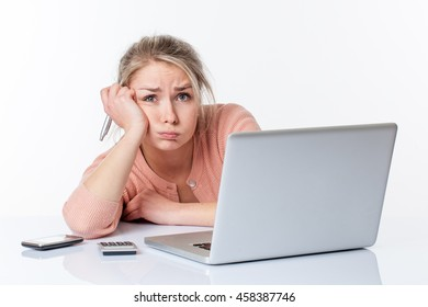 surprised young blond woman leaning on her white sparse desk, puffing out cheeks for exhaustion, working hard on her computer, isolated white background