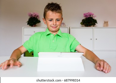Surprised young boy sitting at table and using his white tablet.