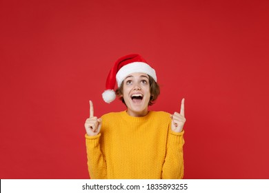 Surprised young brunette Santa woman wearing casual yellow sweater Christmas hat pointing index fingers up isolated on red background studio portrait. Happy New Year celebration merry holiday concept
