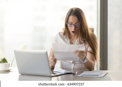 Surprised young businesswoman reading letter at the desk in front of laptop. Woman feels shocked after receiving unexpected news in written message. Female entrepreneur holds notice about loan debt