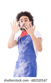 Surprised young chef wearing blue chef uniform, isolated on white background