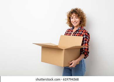 surprised young curly woman in checkered shirt standing on empty wall with some moving boxes