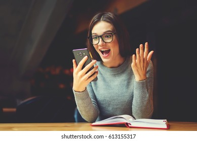 Surprised young female blogger chatting with best friends in social network on mobile phone while received shocking good news using wifi zone and reading interesting book indoors after work
