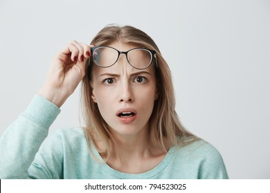 Surprised young female model with long blonde hair, wears glasses and blue long-sleeved shirt, looks with terror at camera as notices something unexpected, hears bad news, isolated against gray wall