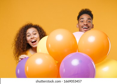 Surprised young friends couple african american guy girl in casual clothes isolated on yellow orange background. Birthday holiday party, people emotions concept. Celebrate hold colorful air balloons