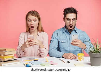 Surprised young friends read shocking news on modern smart phone, sit next to each other, surf social networks, isolated over pink background. Confused puzzled groupmates use mobile phones together