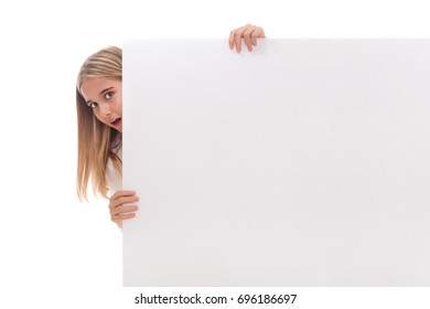 Surprised young girl is popping out from the side of white blank banner over white background