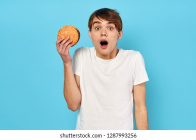 Surprised young guy holding a hamburger in his hands in a white T-shirt on a blue background
