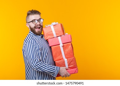 Surprised young hipster guy in glasses holding a large stack of gift boxes on a yellow background with copy space. The concept of New Year and Christmas gifts