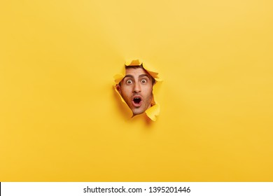 Surprised young man with bristle keeps mouth widely opened, stares through torn paper wall, shows only face, expresses wonder and disbelief, poses against yellow background. Facial expressions