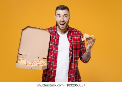 Surprised young man football fan in red shirt cheer up support favorite team with soccer ball italian pizza in cardboard flatbox isolated on yellow background studio. People sport leisure concept