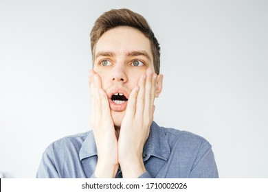 Surprised young man in a gray shirt on a light gray background. Shocked man