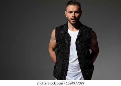 Surprised young man holding both hands at his back while wearing a black jeans vest and standing on gray studio background