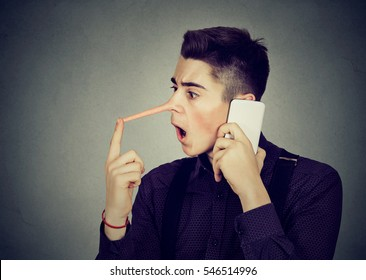 Surprised young man with long nose talking on mobile phone isolated on gray wall background. Liar concept. Human emotion feelings, character traits