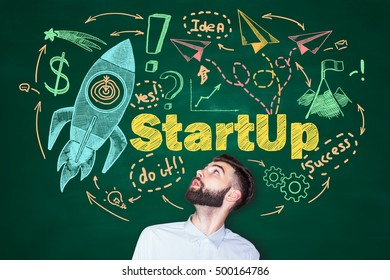 Surprised young man looking up at creative startup sketch on chalkboard background. Start up concept