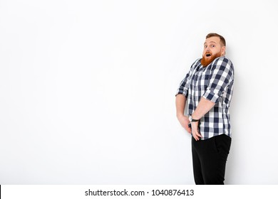 surprised young man with red hair and the beard in front of white wall