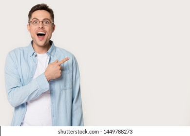 Surprised young man showing by forefinger at blank copy space. Stunned, amazed, astonished male standing pointing aside with index finger wearing glasses looking at camera isolated on gray background