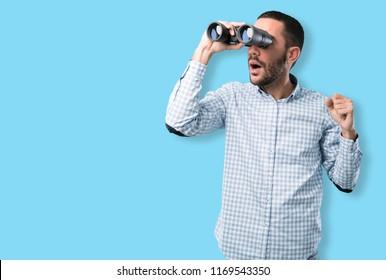 Surprised young man using a binoculars