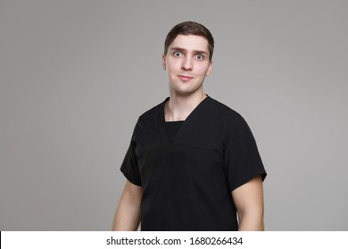 Surprised young white man in casual work black clothes isolated on gray background.