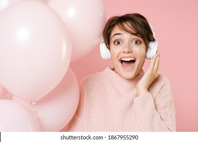 Surprised young woman 20s in knitted casual sweater isolated on pastel pink background. Birthday holiday party people emotions concept. Celebrating hold air balloons listening music with headphones