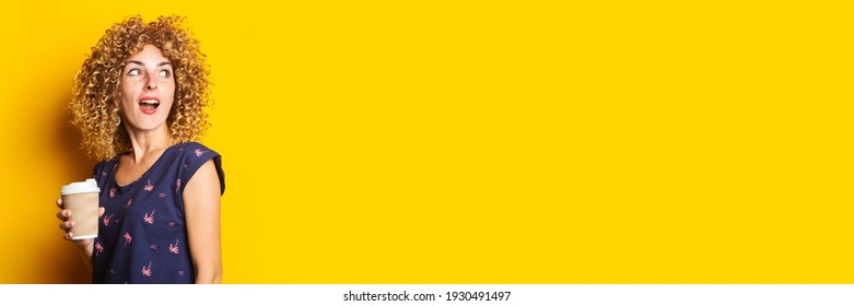 surprised young woman with curly hair holding paper cup on yellow background. Banner