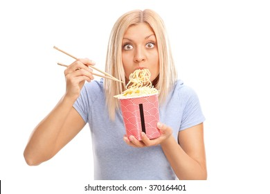 Surprised young woman eating Chinese noodles and looking at the camera isolated on white background
