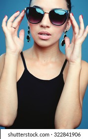 Surprised young woman in glasses over gray background