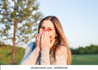 Surprised young woman with hands over her mouth outdoor