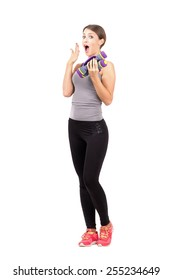 Surprised young woman holding aerobic foam dumb-bells. Full body length portrait isolated over white background.
