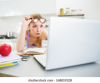 Surprised young woman looking in laptop while studying in kitchen