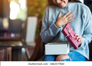 Surprised young woman opening a gift box
