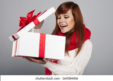 Surprised young woman peeking into the christmas gift