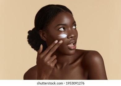 Überraschende junge Frau mit perfekter Hautfarbe kleben Kosmetikcreme auf das Gesicht.  Konzept der Gesichtshaut. Einzeln auf beigem Hintergrund. Studioaufnahme