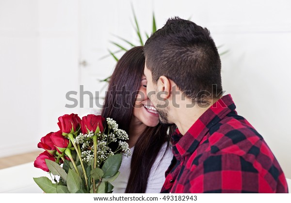 Surprised young woman receiving a bouquet of red roses