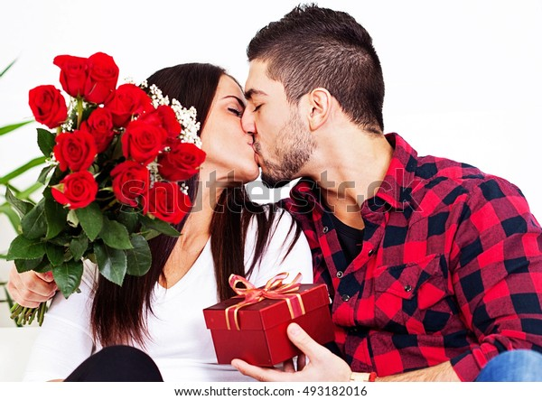 Surprised young woman receiving a gift box and a bouquet of red roses