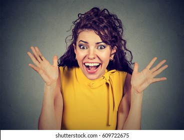 Surprised young woman shouting over gray background. Looking at camera