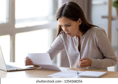 Surprised young woman sitting at desk holding paper reading unbelievable news feels shocked amazed. Received good or bad letter great discount super offer or loan debt, high utility payments concept