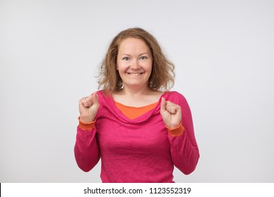 Surprised young woman smiling and holding her hands near face. She is shocked with sale prices. Is it true. She can not believe her eyes.