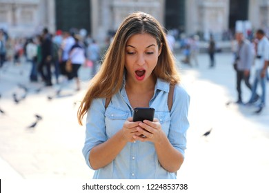 Surprised young woman using smart phone outdoors. Close up portrait surprised screaming girl looking at phone seeing news or photos with funny emotion on her face isolated outside city background.