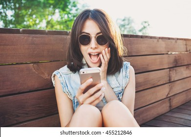 Surprised young woman using smart phone outdoors