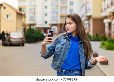 Surprised young woman using smart phone outdoors. Teen girl on the walk.