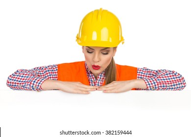 Surprised young woman in yellow hardhat, orange reflective vest and lumberjack shirt posing behind big white poster and looking down. Studio shot isolated on white.