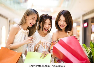 Surprised young women looking the shopping  bags