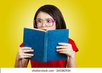 Surprised,Amazed cute little schoolgirl  with a open book on her head, isolated over yellow background.