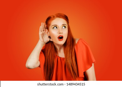 Surprising, shocking news. A woman heard something interesting holding her hand to her ear trying to hear isolated Red background