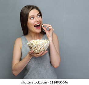 Surprising woman eating popcorn. Girl holding big glass bowl with cinema portion of pop corn.