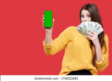 Surprized exciting woman holding mobile phone or smartphone with blank green screen and dollar banknotes, female with money, girl playing bet online casino, isolated on red